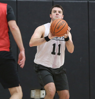 Adult Basketball League in Boston Male Player crouches to shoot basketabll