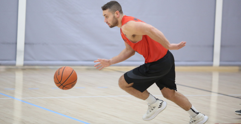 Adult Basketball League in Boston Player in red dribbles basketball up court