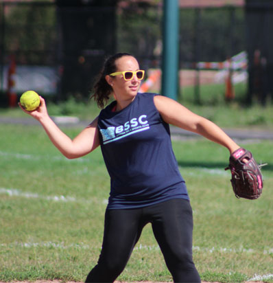 BSSC Sports Outdoor Coed Softball League in Boston, MA a female player in orange sunglasses and a blue jersey with the sleeves rolled up winds up to throw softball to teammate