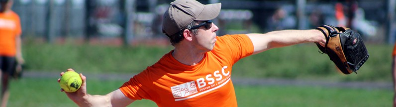 BSSC Softball Male softball player standing on mound in bright orange tee jersey and sunglasses winds up to pitch softball at batter