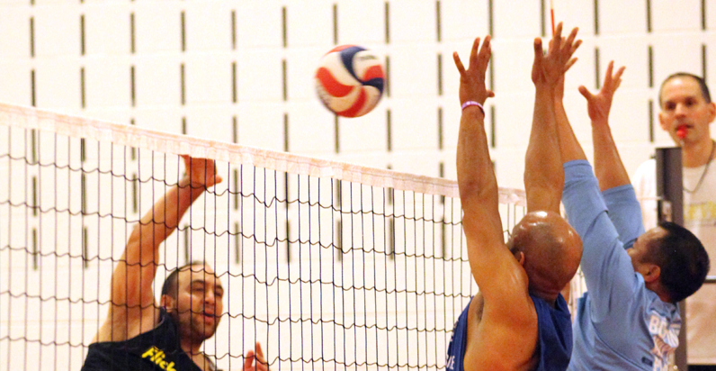BSSC indoor adult volleyabll players jump tp block opponant as he spikes the ball