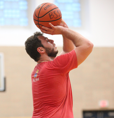 Adult Basketball League in Boston Man Holds basketball over his head to aim and shoot