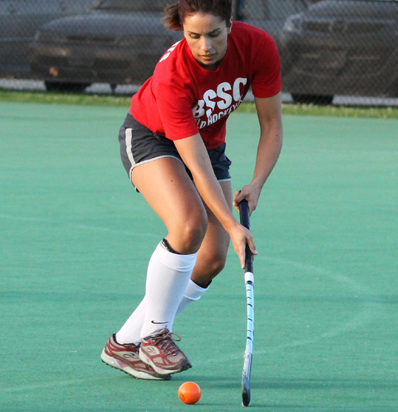 BSSC Field Hockey Adult Women's Field Hock league in Boston, MA Woman in Red Tee Shirt Jersey Runs with Ball
