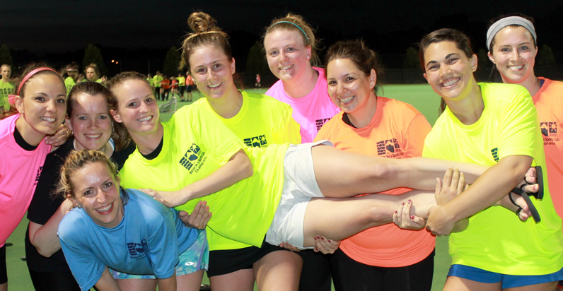 BSSC Women's Field Hockey Adult Field Hockey League in Greater Boston Team of Women in Neon Jerseys Smile for Championship Photo While Holding Teammate Sideways
