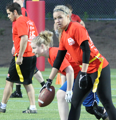 BSSC Football Coed Adult Football League in Boston, MA Blonde Female Football Player Holds Football Out in Front of Her and Looks at Camera