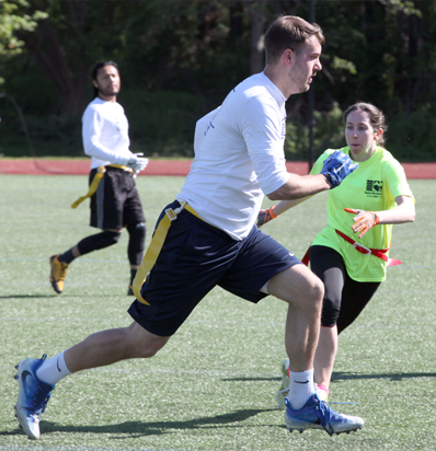 BSSC Football Adult Coed Flag Football League in Boston, MA Male Player in White Long Sleeve Tee Runs Down Football Field