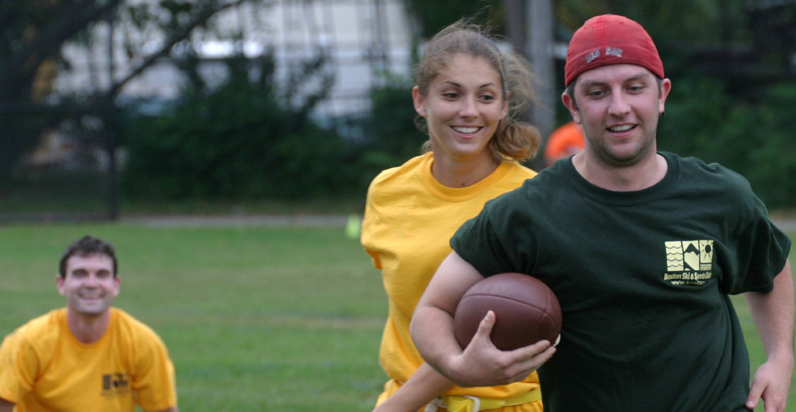 BSSC Coed Football Adult Recreational Football League in Boston, MA Male Player Runs Holding Football Under Arm Female PLayer in Yellow Smiles Running After Opponent Holding Football