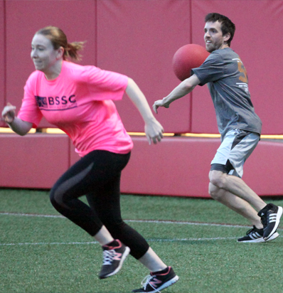 BSSC Kickball League Man In Grey tee SHirt Jersey Aims to Throw Ball at Female Player in Hot Pink Tee Shirt Jersey Running Away