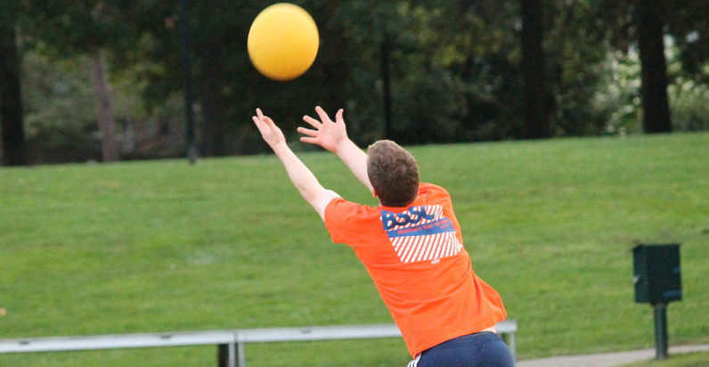BSSC Kickball Player in orange runs through grass and reaches for a falling ball