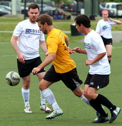 BSSC Soccer Adult Coed Soccer League in Boston, MA Man in Yellow Jersey Dribbles Soccer Ball Away From Opposing Players in White Jerseys Surrounding Him
