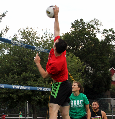 BSSC Volleyball Coed Adult Volleyball League in Boston Male Player in Red Tee Shirt Jumps to Spike Volleyball Over Net