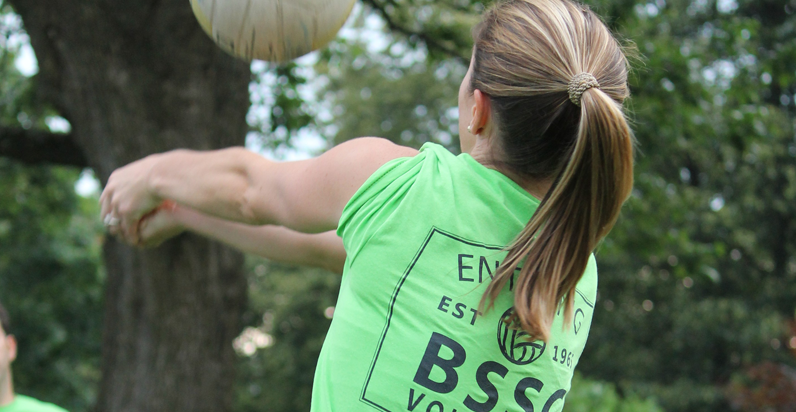 BSSC Volleyball Outdoor Tournament in Boston, MA Female Player in Green Tee Shirt Jersey and Ponytail From Behind Bumps Passes Volleyball