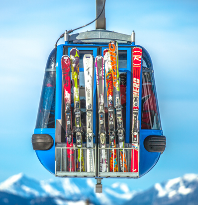Gondola loaded with skis against a blue sky