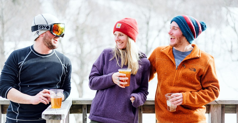 BSSC Ski & Ride Adult Coed Friends in beanies and ski goggles laugh with beers in hand