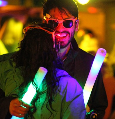 BSSC Couple Dance at Rock the Boat Party Cruise Man in Sunglasses Dances with Woman While Both Hold Foam Glowsticks