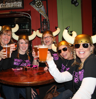 BSSC Winter Warrior Pub Crawl Group in Viking Helmets holding beers at Boston bar