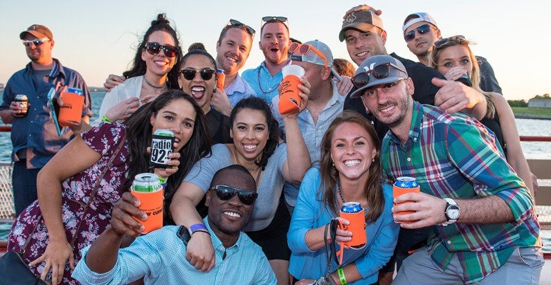 BSSC Social Events Rock the Boar Party Cruise Group of Young Adults Holding Beer in Koozies and Smiling on a Boat in Boston, MA