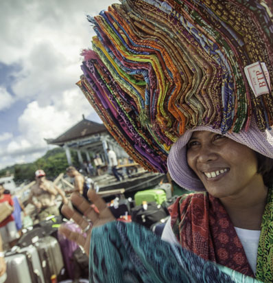 BSSC Travel Beautiful Woman Holds Bright Textiles and Fabric Abover Her Head and Smiles