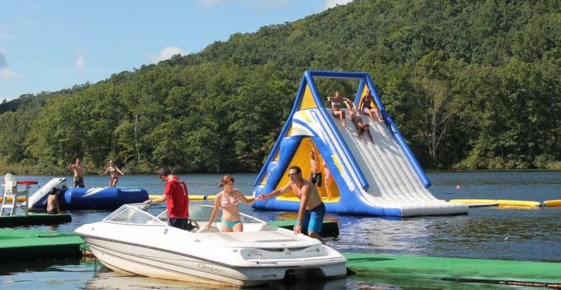 Men and Women in Bathing Suits on Lake in Mountains with green Trees Surrounding Them on Boats and Inflatable Slide and Lake Toys