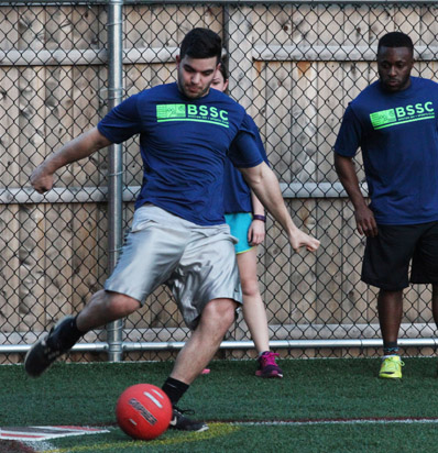 BSSC Sports Adult Kickball Coed League in Boston Male Player kicks the kickball as players on deck watch