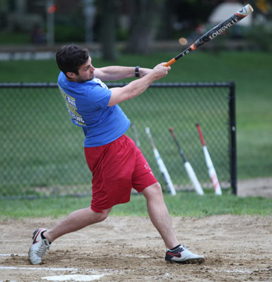 BSSC Outdoor Softball Male Player in Purple jersey and red shorts swings softball bat