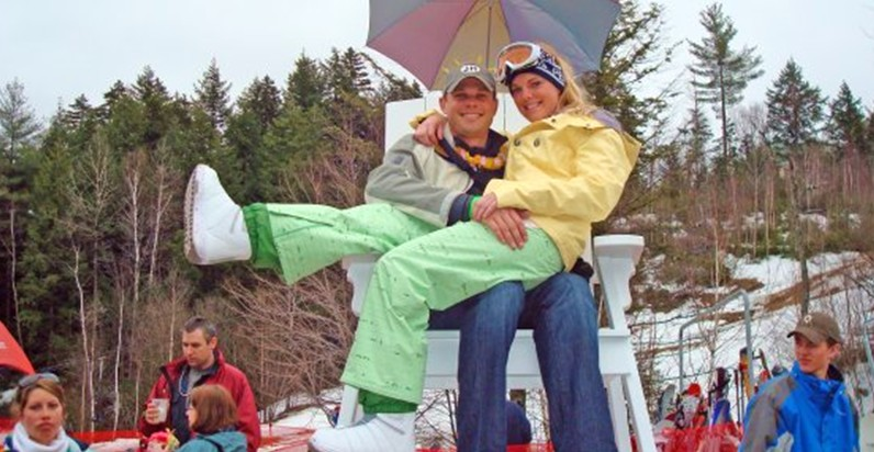 Couple in Snow Gear Smiling in Mountains Woman in Yellow Snowboard Pants Sits on Man's Lap in White Chair Outside