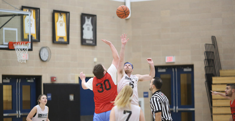 BSSC Sports Coed Adult Basketball League Male Players jump for a jump ball while teammates focus in background