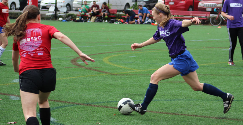 BSSC Soccer Women's Soccer League in Boston Female Player in purple shorts and jersey dribbles the soccer ball at opponents in red jerseys