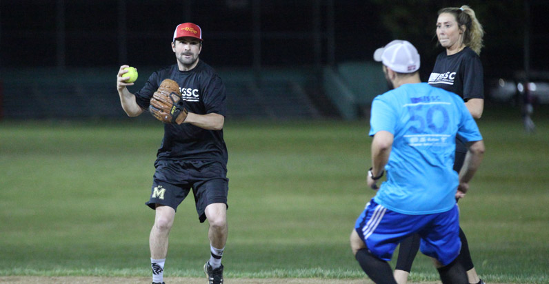 BSSC Softball Adult coed softball league in Boston a male player winds to throw ball while opponents run