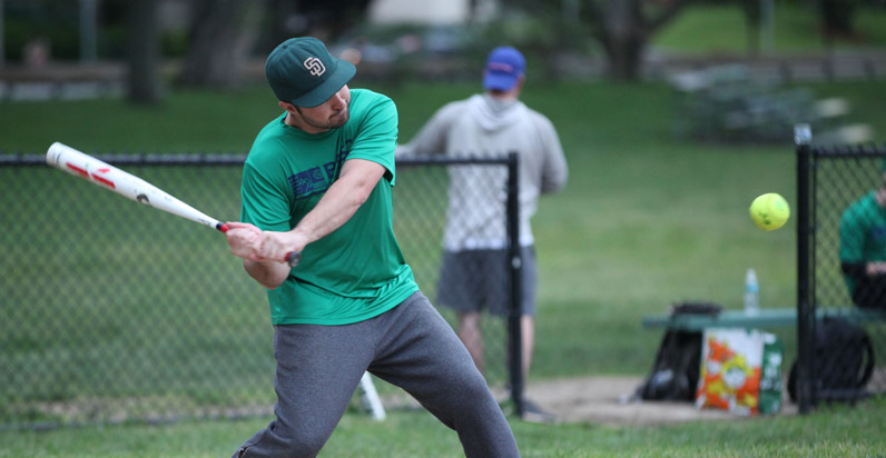 BSSC Coed Outdoor Softball PLayer in green jersey swings at approaching ball
